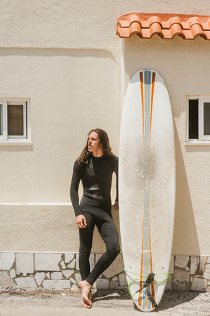 young man with long hair in wetsuit standing on street near surfing board in Portugal