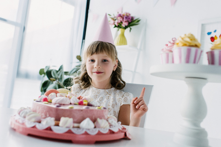 happy child in cone doing idea gesture at table with birthday cake
