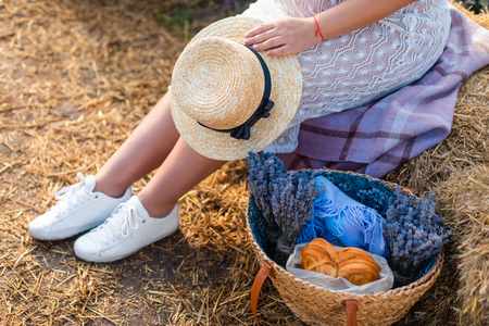 Cropped image of woman sitting in white dress on hay bale and holding straw hat Stock Photo