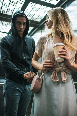 male robbery pickpocketing smartphone from bag of woman with coffee in elevator Фото со стока