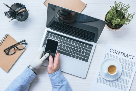 cropped image of businessman with prosthetic arm checking smartphone at table with laptop in office