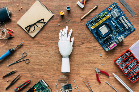 top view of prosthetic arm on wooden table with tools, spectacles and textbook 스톡 콘텐츠 - 105705627