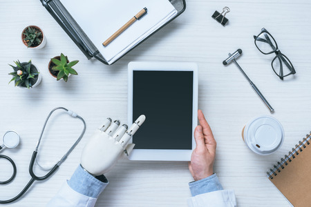 partial view of male doctor with prosthetic arm using digital tablet with blank screen
