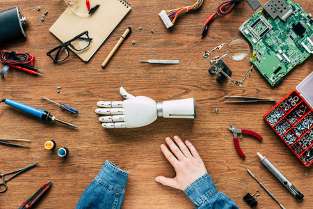 cropped image of man with amputee sitting at table with prosthetic arm surrounded by instruments Stock Photo