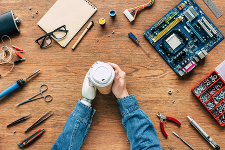 cropped image of electronic engineer with prosthetic arm holding paper cup on table with tools Stock Photo