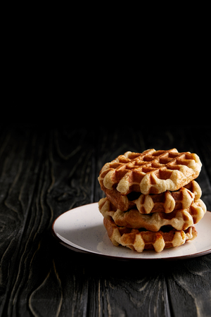 stack of freshly baked belgian waffles on plate on black wooden table