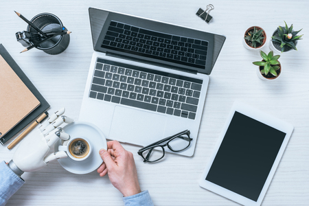 cropped image of businessman with prosthetic arm drinking coffee at table with laptop, digital tablet and eyeglasses Stock Photo