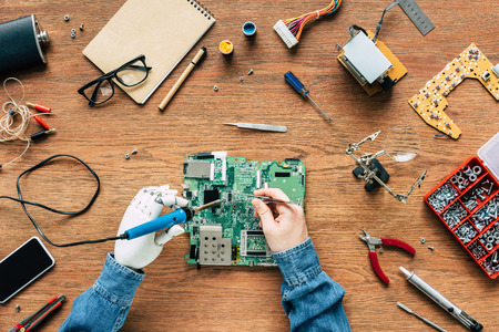 cropped image of electronic engineer with prosthetic arm fixing motherboard by soldering iron and tweezers Stock Photo