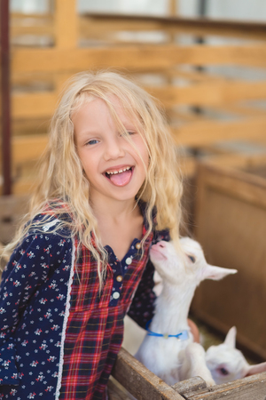 kid sticking tongue out and hugging goat at farm Foto de archivo - 105705775