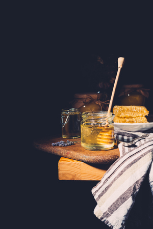 selective focus of honey stick in jar with honey on cutting board at table on black background