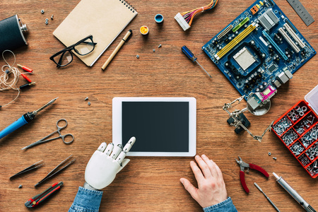 cropped image of man with robotic hand using digital tablet at table surrounded by tools