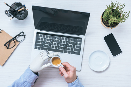 partial view of businessman with prosthetic arm drinking coffee at table with laptop in office
