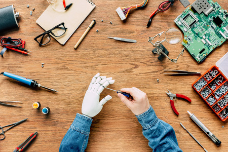 cropped image of man fixing prosthetic arm by screwdriver at wooden table Stock Photo