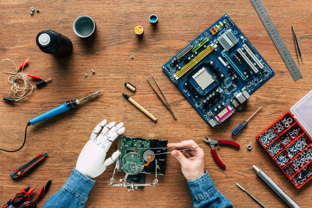 cropped image of man with robotic hand repairing hard drive by tweezers