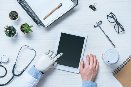 cropped image of male doctor with prosthetic arm using digital tablet with blank screen at table with medical tools