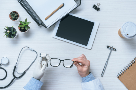 cropped image of male doctor with prosthetic arm holding eyeglasses at table with blank digital tablet
