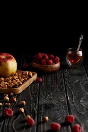hazelnuts with apple and raspberries on black wooden table