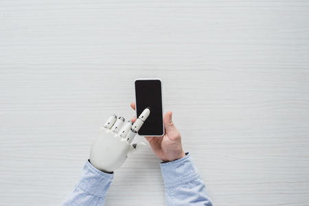 cropped image of man with cyborg hand using smartphone with blank screen over wooden table