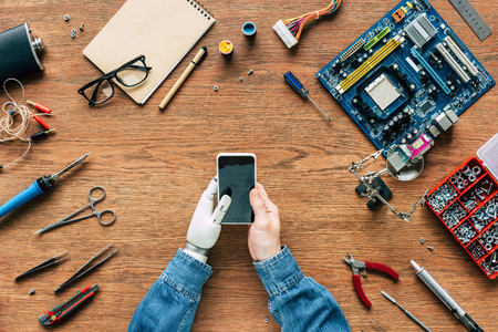 cropped image of  electronic engineer with prosthetic arm using smartphone at table surrounded by tools