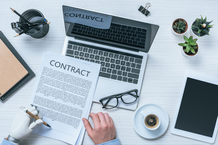 cropped image of businessman with prosthetic arm signing contract at table Stock Photo