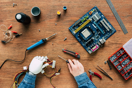 cropped image of man with prosthetic arm holding wires and screwdriver surrounded by instruments on wooden table