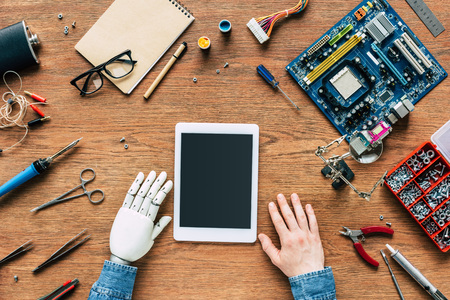 cropped image of  electronic engineer with robotic hand sittng at table with digital tablet surrounded by tools Stock Photo