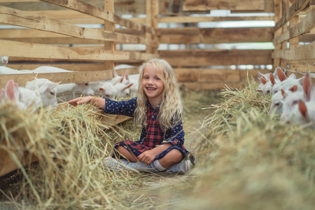 smiling kid sitting on ground near goats in barn and looking at camera
