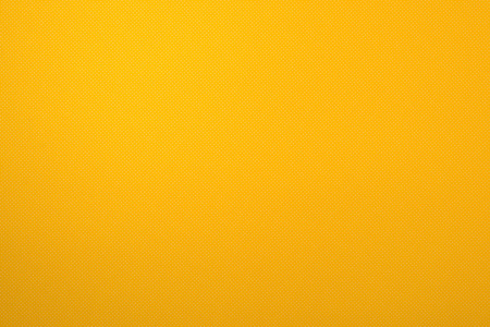 top view of yellow surface with tiny white polka dot pattern for background