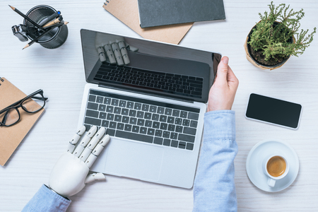 cropped image of businessman with prosthetic arm opening laptop at table in office