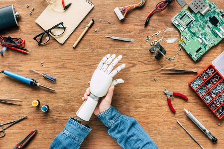 cropped image of man with amputee putting on robotic hand on table with tools Stock Photo