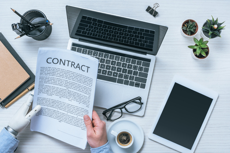 cropped image of businessman with prosthetic arm reading contract at table in office Stock Photo