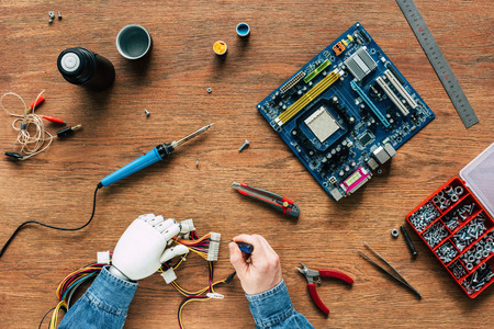 cropped image of man with prosthetic arm repairing wires by screwdriver at wooden table
