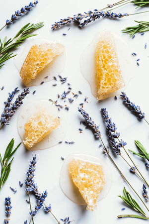 elevated view of honeycombs, lavender and rosemary on white table