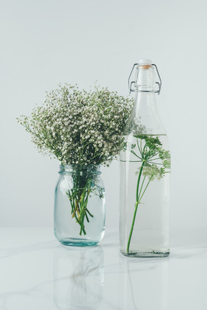 glass bottle with water and dill and glass jar with flowers on white table Banco de Imagens