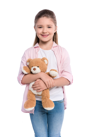 Half-length shot of a smiling little girl holding a teddy bear and looking at camera