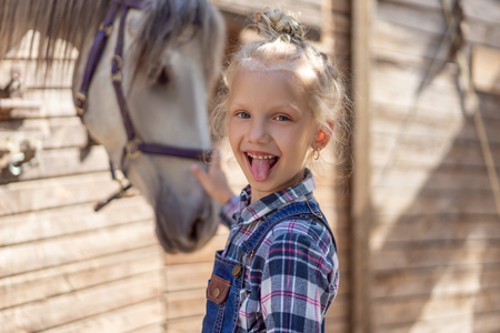 kid sticking tongue out and palming horse at farm