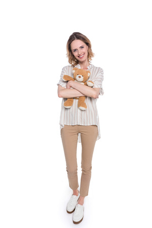 Full-length shot of a smiling young woman hugging a teddy bear and looking at camera