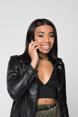 Half-length shot of cheerful young woman talking on the phone and looking at camera