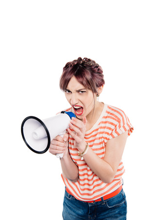 portrait of shouting young woman with loudspeaker looking at camera isolated on white
