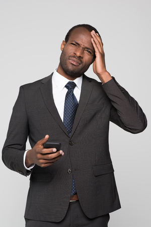Half-length shot of businessman in a suit with phone in his hand touching his head and squinting in pain. Reklamní fotografie