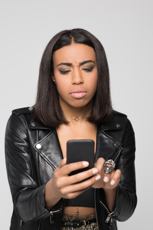 Half-length shot of young woman typing on her smartphone with irritated look on her face.