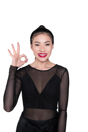 young asian woman showing okay sign isolated on white