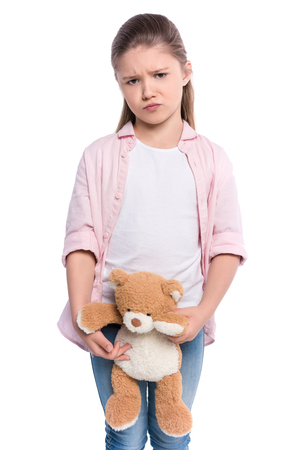 Half-length shot of a little girl holding a teddy bear with a grumpy look on her face