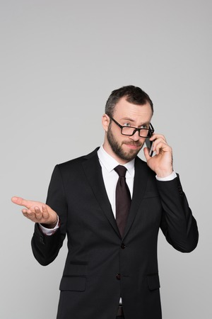 Half-length shot of young businessman in a suit talking on the phone with interrogative look on his face. Stock Photo