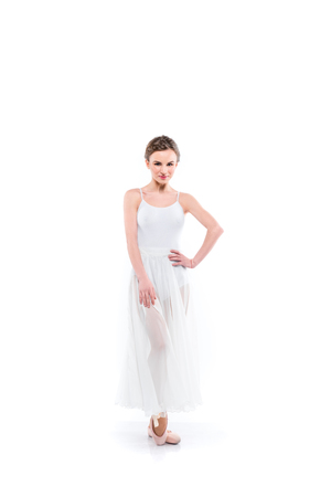 smiling ballet dancer posing in white tutu and pointe shoes, isolated on white