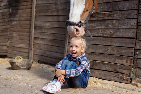 happy kid sitting on ground and horse touching her hair at farm Stock Photo