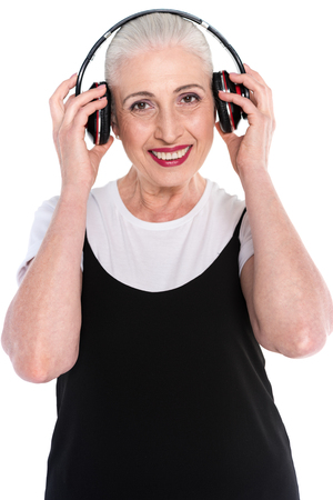 Half-length shot of a senior woman listening to music in big headphones and looking at camera