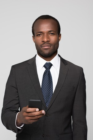 Half-length shot of businessman in a suit holding smartphone in his hand and looking at camera