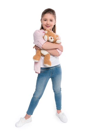 Full-length shot of a little girl hugging a teddy bear and looking at camera