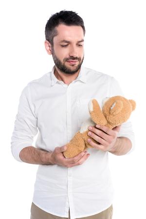 Half-length shot of a young bearded man holding a teddy bear